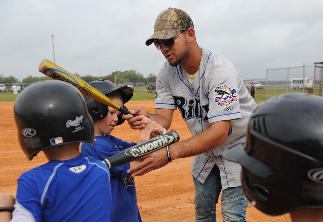 Javier Betancourt, Biloxi Shuckers second baseman, shows Keesler children how to grip a bat during the Biloxi Shucker's Youth Baseball Clinic at the youth center baseball field April 30, 2016, Keesler Air Force Base, Miss. The clinic provided hitting, pitching, base running and fielding instruction from members of the Biloxi Shucker's minor league baseball team. (U.S. Air Force photo by Kemberly Groue)