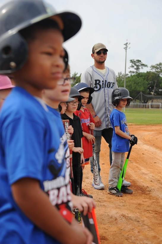 Javier Betancourt, Biloxi Shuckers second baseman, stands with Keesler children before swinging practice during the Biloxi Shucker's Youth Baseball Clinic at the youth center baseball field April 30, 2016, Keesler Air Force Base, Miss. The clinic provided hitting, pitching, base running and fielding instruction from members of the Biloxi Shucker's minor league baseball team. (U.S. Air Force photo by Kemberly Groue)