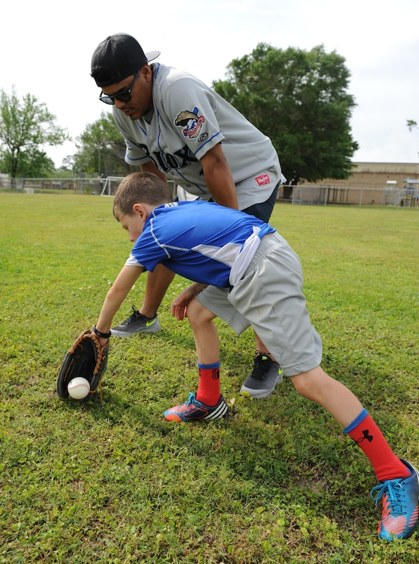 L.J. Reents, son of Master Sgt. Jamie Cleveland, 81st Surgical Operations Squadron physical therapy NCO in charge, receives fielding technique instruction from Rene Garcia, Biloxi Shuckers catcher, during the Biloxi Shucker's Youth Baseball Clinic at the youth center baseball field April 30, 2016, Keesler Air Force Base, Miss. The clinic provided hitting, pitching, base running and fielding instruction from members of the Biloxi Shucker's minor league baseball team. (U.S. Air Force photo by Kemberly Groue)