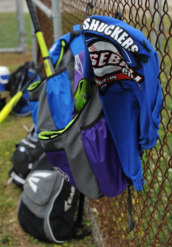 Baseball equipment and a T-shirt hangs from a fence during the Biloxi Shucker's Youth Baseball Clinic at the youth center baseball field April 30, 2016, Keesler Air Force Base, Miss. The clinic provided hitting, pitching, base running and fielding instruction from members of the Biloxi Shucker's minor league baseball team.  (U.S. Air Force photo by Kemberly Groue)