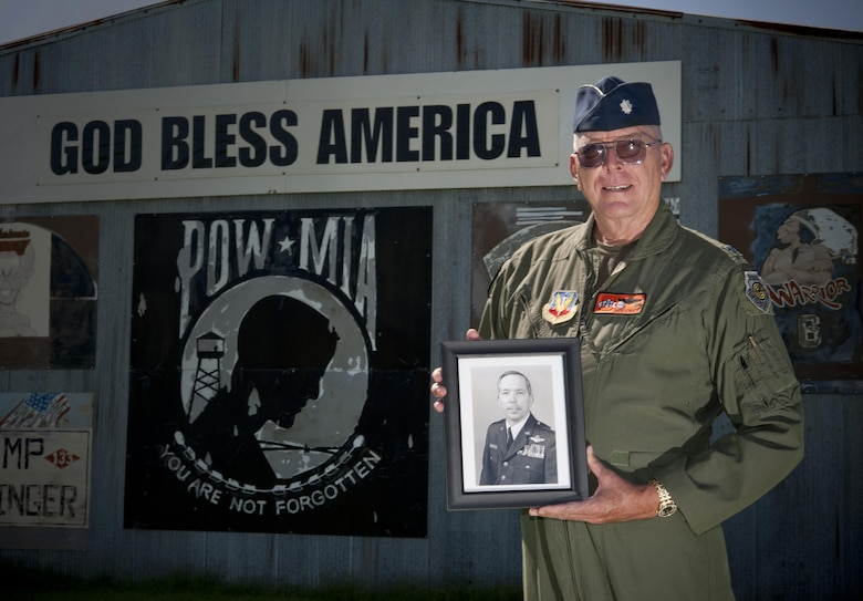 "Retired Lt. Col. Bill ""Shortfinger"" Schwertgege, an F-4 Phantom pilot and Vietnam War POW, points to Neil S. Bynums Name on the Woodring Wall of Honor, at Woodring Regional Airport, Enid Oklahoma. The Woodring Wall was won of the two traveling Vietnam War Memorial Walls. it is a 90 percent replica of the original memorial in Washington D.C. it found a permenant home in Enid in 2013. Schwertfeger served with Bynum, who is still missing in action in Vietnam, and wears Bynum's POW/MIA bracelet. (U.S. Air Force photo/Staff Sgt. James Bolinger)"