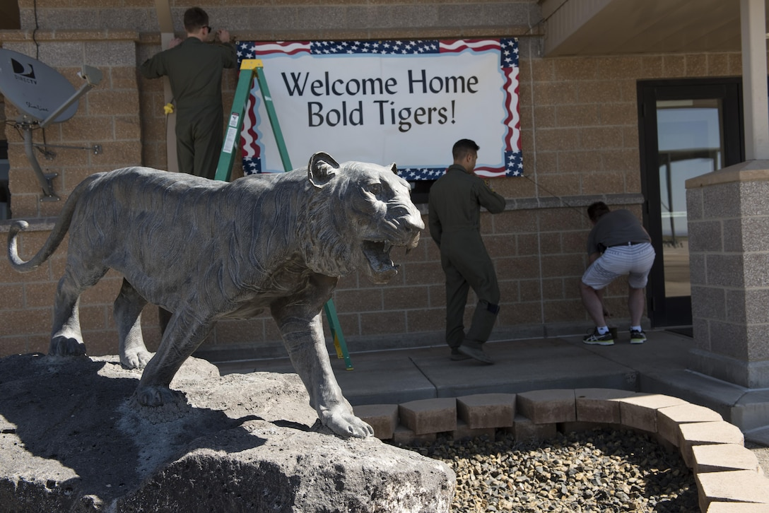 """Members of the 391st Fighter Squadron hang a """"Welcome Home"""" sign behind a statue of the squadron mascot at Mountain Home Air Force Base, Idaho, April 17, 2016. Airmen deployed to Southwest Asia in support of Operation Inherent Resolve. (U.S. Air Force photo by Airman Alaysia Berry/Released)"""