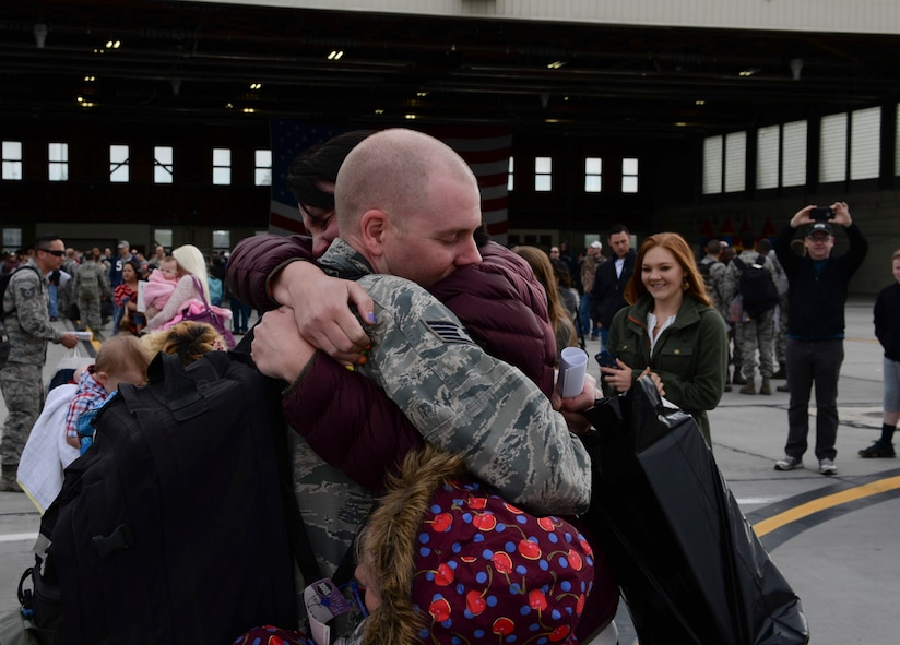 A family embraces for the first time following a deployment April 24, 2016, at Mountain Home Air Force Base, Idaho. Airmen returned after serving six months in Southwest Asia. (U.S. Air Force photo by Airman 1st Class Chester Mientkiewicz/Released)
