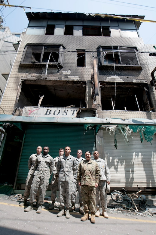 Team Osan members pose near the building that caught fire at Songtan shopping district, Republic of Korea, May 2, 2016. The Airmen and Soldiers, along with many onlookers worked together to save the lives of an Airmen, mother and her three children when a fire broke out on April 29, 2016. (U.S. Air Force photo by Staff Sgt. Jonathan Steffen/Released