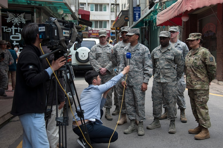 Local media interviews Team Osan members that rescued people from a fire at Songtan shopping district, Republic of Korea, May 2, 2016. The Airmen and Soldiers, along with many onlookers worked together to save the lives of an Airmen, mother and her three children when a fire broke out on April 29, 2016. (U.S. Air Force photo by Staff Sgt. Jonathan Steffen/ Released)