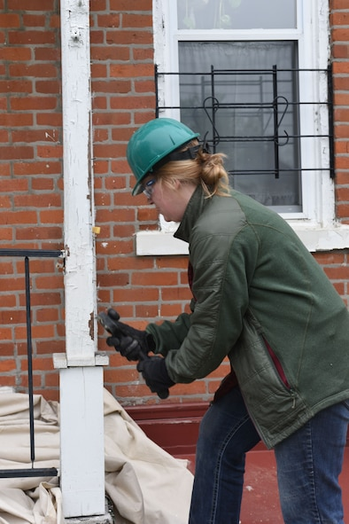 U.S. Air Force Tech Sgt. Cathy Hammett, with the 121st Logistics Readiness Squadron, chips away at old paint during a community outreach program with Habitat for Humanity April 23, 2016 Columbus, Ohio. EFAC Airmen helped to build a new walkway railing, repaint window sills and replace old windows for a local family in need. (U.S. Air National Guard photo by Airman 1st Class Ashley Williams/Released)