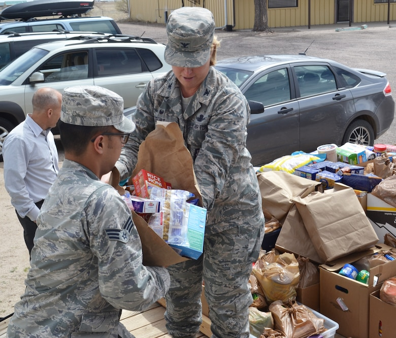 Col. DeAnna Burt, 50th Space Wing commander (right), transfers food to Senior Airman Matthew Sarangay, 50th Contracting Squadron, during a donation drop-off at the Ellicott Helping Hands Food Pantry in Ellicott, Colorado, Tuesday, April 26, 2016. The food was collected by the Schriever Air Force Base Teens/Kids Helping Kids group during a food drive at the Peterson Air Force Base commissary April 23-24. The group raised more than $350 and 2,149 pounds of food to benefit local families. (U.S. Air Force photo/Brian Hagberg)
