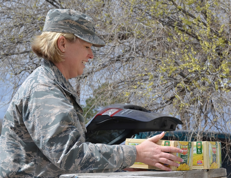 Col. DeAnna Burt, 50th Space Wing commander, stacks cases of canned corn outside the Ellicott Helping Hands Food Pantry in Ellicott, Colorado, Tuesday, April 26, 2016. The corn was part of the 2,149 pounds collected by the Schriever Air Force Base Teens/Kids Helping Kids during a food drive at the Peterson Air Force Base commissary April 23-24 and will benefit local families. (U.S. Air Force photo/Brian Hagberg)