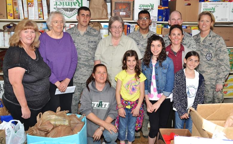 Col. DeAnna Burt, 50th Space Wing commander (right), stands in front of the fully stocked shelves at the Ellicott Helping Hands Food Pantry with pantry workers and volunteers from the Schriever Air Force Base Teens/Kids Helping Kids following a donation to the pantry in Ellicott, Colorado, Tuesday, April 26, 2016. The Teens/Kids Helping Kids group held a food drive at the Peterson Air Force Base commissary April 23-24 and raised more than $350 and collected 2,149 pounds of food for the pantry. (U.S. Air Force photo/Brian Hagberg)