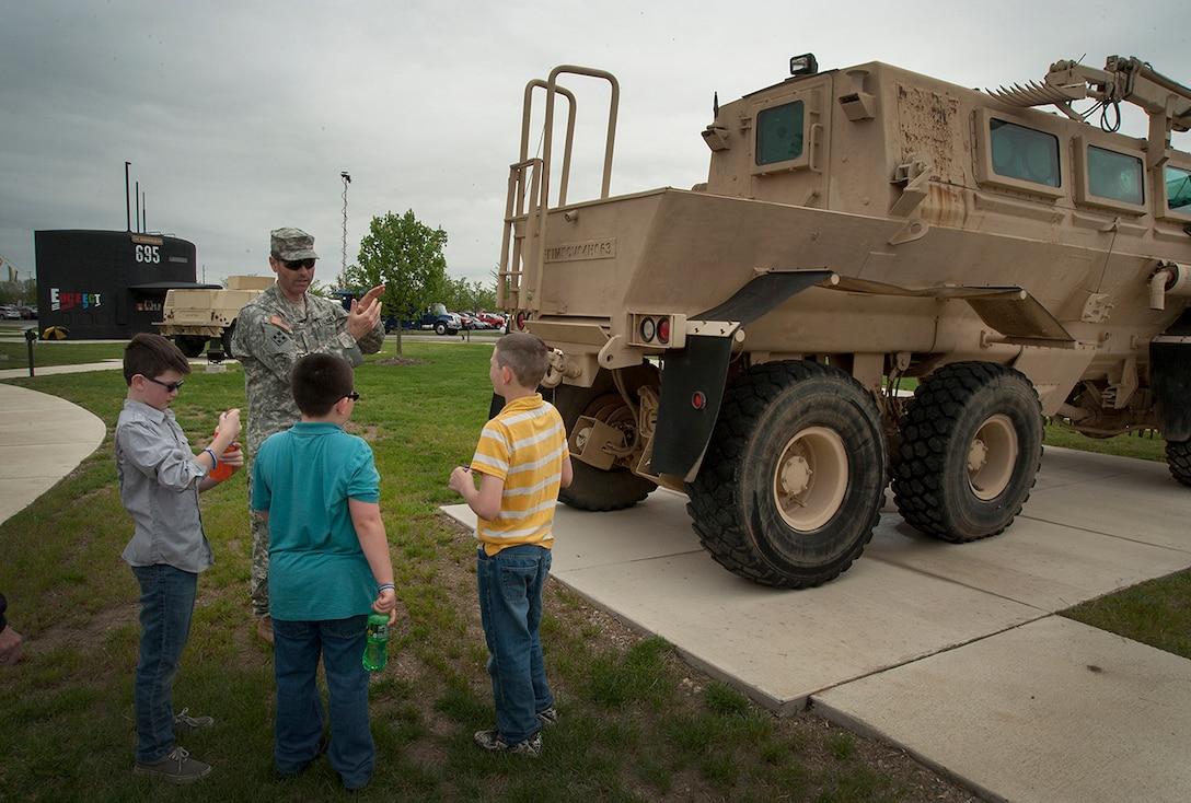 Maj. Jeffrey Scott, Land and Maritime, shows a family the intricacies about a Land Mine sweeper used in combat that now sits indie DSCC's Mission Park.