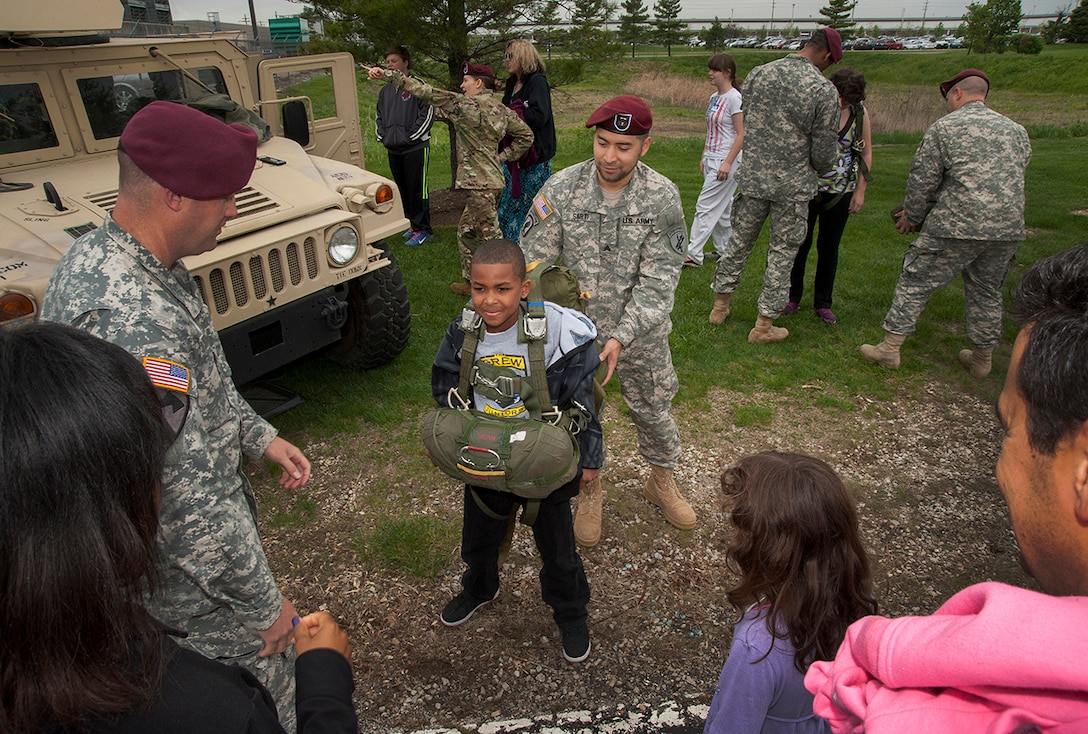 Aspiring para trooper is fitted with the parachute assembly used by service members during flight jumps. Several parents and their kids took the opportunity to harness up as part of their orientation about different jobs parents perform on the installation.
