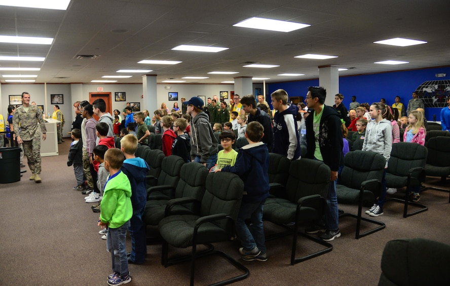 "Participating children stand to greet Col. Ben Maitre, 27th Special Operations Wing commander, upon arrival for Operation KUDOS (Kids Understanding Deployment Operations) April 30, 2016, at Cannon Air Force Base, N.M. After receiving a mission brief from Maitre, 97 children headed out to their ""deployed location"" and interacted with various supporting agencies. (U.S. Air Force photo/Staff Sgt. Alexx Pons)"