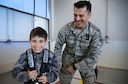 Senior Airman John Saucedo, 27th Special Operations Civil Engineer Squadron emergency management, helps a child try on an oxygen tank during Operation KUDOS (Kids Understanding Deployment Operations) April 30, 2016, at Cannon Air Force Base, N.M. Multiple agencies and displays were made available to highlight the wing's extensive mission-supporting capabilities. (U.S. Air Force photo/Staff Sgt. Alexx Pons)