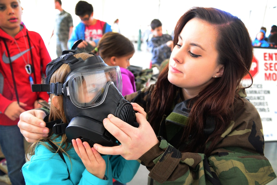 Airman 1st Class Amanda Kopecky, 27th Special Operations Civil Engineer Squadron emergency management, helps a child try on a gas mask during Operation KUDOS (Kids Understanding Deployment Operations) April 30, 2016, at Cannon Air Force Base, N.M. Children interacted with multiple agencies and displays to better understand their roll in the wing's mission. (U.S. Air Force photo/Staff Sgt. Alexx Pons)