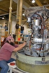 """Michael Beeskau, an aircraft engine mechanic repairs a TF-34 engine March 4, 2015 at the Crinkley Engine Facility on Fleet Readiness Center Southeast in Jacksonville, Florida. The engine powers the U.S. Air Force A-10 Thunderbolt """"Warthog"""" aircraft"""