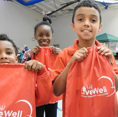 Joseph Clark, 8, holds his Kids LiveWell goodie bag, which was presented to children and teenagers who attended the kick off of Kids LiveWell, a partnership among the Air Force, the National Restaurant Association and Sysco Foods, on April 14 at Joint Base San Antonio-Lackland. (U.S. Air Force photo/Steve Warns/released)