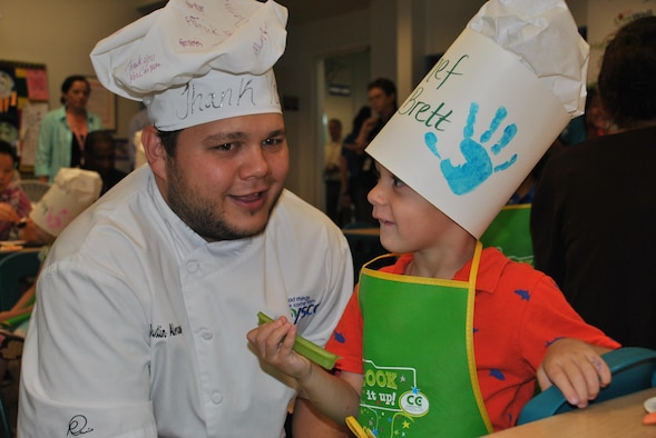 """Dustin Alexander, a chef with Sysco Foods, visits with """"Chef Brett"""" during the kickoff of Kids LiveWell at Joint Base San Antonio-Lackland on April 21. Alexander whipped up a yogurt-based dip for celery and carrot sticks during the presentation. (U.S. Air Force photo/Carole Chiles Fuller/Released)"""