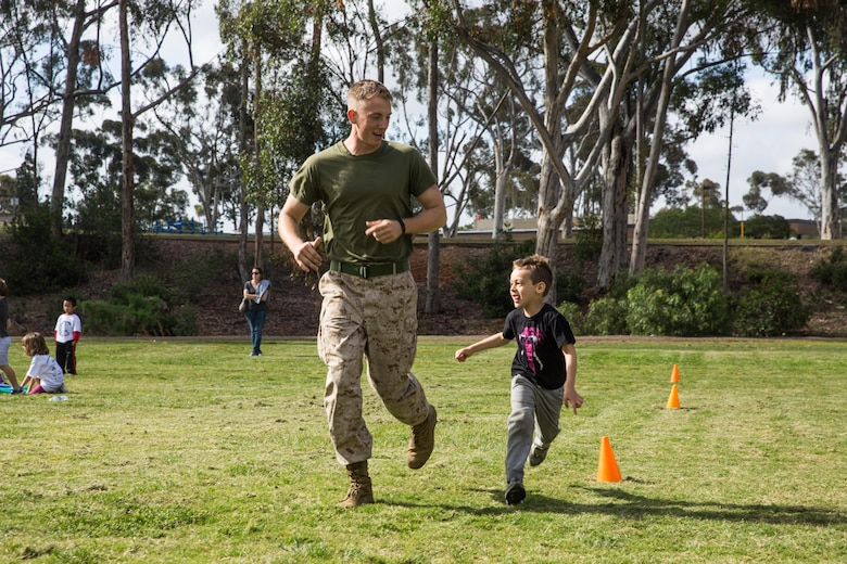Cpl. Christoph Warner, a volunteer with the Single Marine Program aboard Marine Corps Air Station Miramar, and a Denton, Texas, native, runs alongside a student at Miramar Ranch Elementary School in San Diego, April 29. The Marines volunteered for a P.E. Fitness Challenge, an event which allowed children and Marines to complete a series of exercises throughout the course of the school day. (U.S. Marine Corps photo by Sgt. Lillian Stephens/Released)