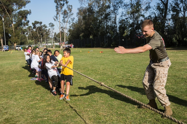 Lance Cpl. Chase McManaman, a volunteer with the Single Marine Program aboard Marine Corps Air Station Miramar, and a Hinton, Okla., native, declares the winner of a tug of war competition at Miramar Ranch Elementary School in San Diego, April 29. The Marines volunteered for a P.E. Fitness Challenge, an event which allowed school-age children and Marines to complete a series of exercises throughout the course of the school day. (U.S. Marine Corps photo by Sgt. Lillian Stephens/Released)