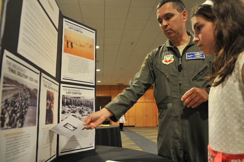 Lt. Col. Luis Montealegre, 1st Air Force A9 deputy director, reads holocaust information with his daughter Cristina Montealegre during the Holocaust Remembrance Day event May 4 at the Horizons Community Center. The event is also known in the Hebrew language as Yom Hashoah. The day corresponds with the 27th day of Nisan on the Hebrew calendar which means the day falls on different days of the year within the standard 365 day calendar year. (U.S. Air Force photo by Senior Airman Ty-Rico Lea/Released)