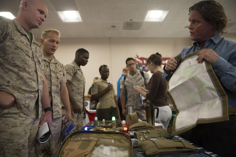 Greg Kennedy, Tactical Lighting Solutions representative, shows off the Lazer Brite Tactical Pouch to Marines during the Combat Center's Sustainability Expo at the Frontline Restaurant April 26, 2016. (Official Marine Corps photo by Cpl. Connor Hancock/Released)