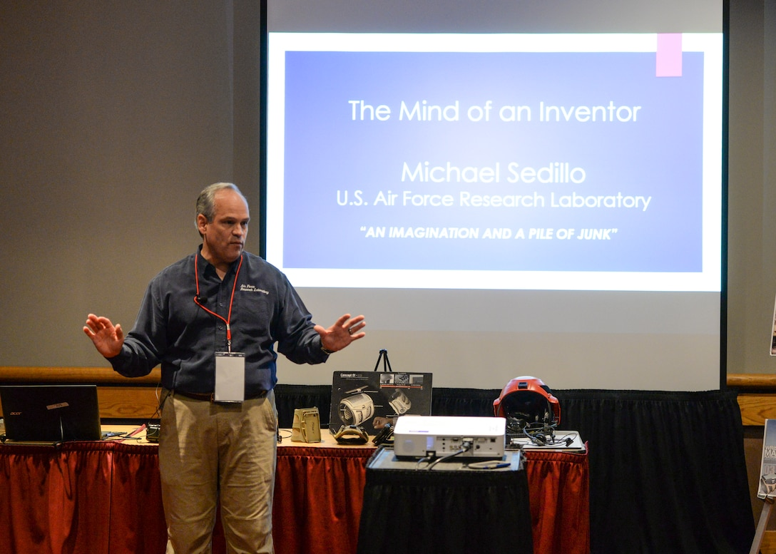 Michael Sedillo, a program analyst with the Air Force Research Laboratory Battlefield Air Targeted Man Aided Knowledge Program, delivers a speech about inventing wearable technology being researched and developed to a room of more than 40 students during the 54th National Junior Science and Humanities Symposium inside the Dayton Convention Center April 28. JSHS is a tri-service, U.S. Army, Navy and Air Force, program that encourages high school students to conduct original research in the fields of science, technology, engineers and mathematics (STEM). (U.S. Air Force photo/Wesley Farnsworth)