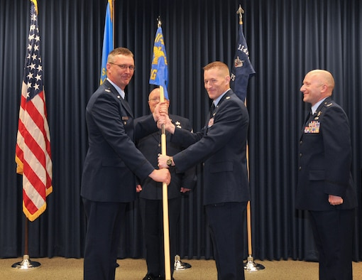 Col. Nate Alholinna, 114th Fighter Wing commander, passes the 114th Operations Group guidon flag to Lt. Col. Quenten Esser as he assumes command of the 114th Operations Group effective May 1, 2016. (U.S. Air National Guard photo by Master Sgt. Christopher Stewart/Released)