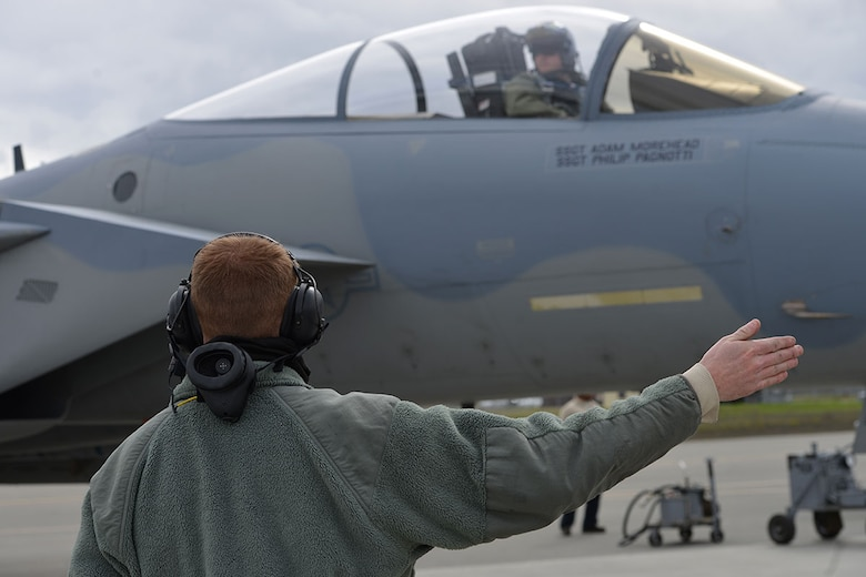 Air Force Staff Sgt. Austin Hamilton, 96th Aircraft Maintenance Squadron F-15 crew chief, from Eglin Air Force Base, Fla., signals an F-15 Eagle pilot while preparing departure on the Joint Base Elmendorf-Richardson flightline, May 3, 2016. Hamilton is deployed to JBER as part of Red Flag-Alaska, a Pacific Air Forces commander-directed field training exercises for U.S. and international forces, providing combined offensive counter-air, interdiction, close air support and large force employment training in a simulated combat environment. (U.S. Air Force photo by Airman 1st Class Javier Alvarez)