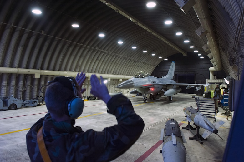 Staff Sgt. Corey Spencer, 80th Aircraft Maintenance Unit crew chief, marshals an F-16 Fighting Falcon from the 35th Fighter Squadron Beverly Midnight 16-3 at Kunsan Air Base, Republic of Korea, May 4, 2016. The exercise tested Airmen on their ability to survive and operate while under the stress of simulated wartime activities all while ensuring aircraft generate. (U.S. Air Force photo by Staff Sgt. Nick Wilson/Released)