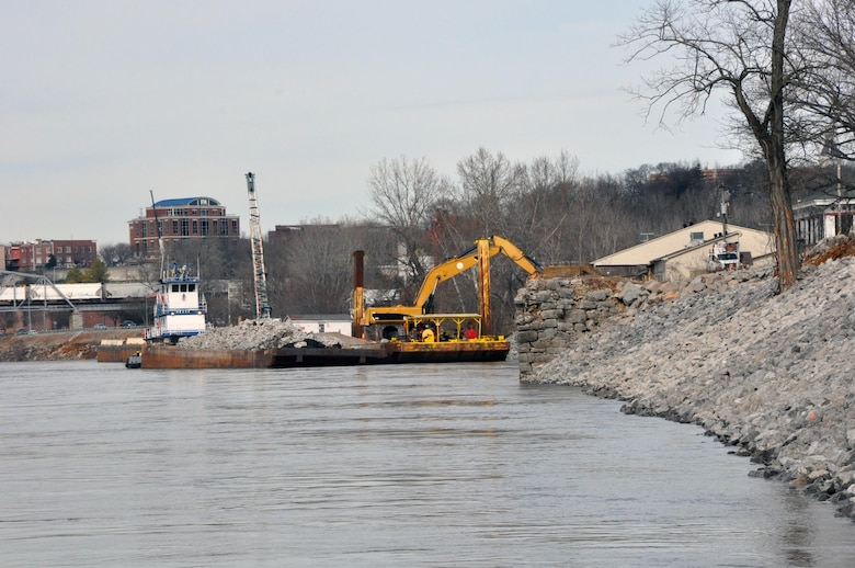Crews from the Choctaw Transportation, Inc. from Dyersburg, Tenn., cleared and prepared the bank along the Cumberland River in Clarksville, Tenn., and used barges equipped with backhoe tractors to place a layers of geotextile fabric and riprap with limestone rock to stabilize the eroding bank. The project is part of the Riverside Drive Stream Bank Stabilization Project.