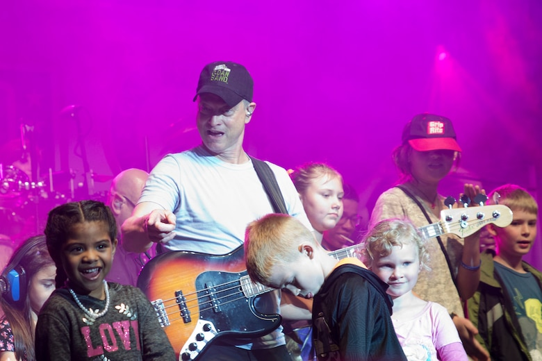 Surrounded by children, actor and musician, Gary Sinise, performs with the Lt. Dan Band at Little Rock Air Force Base, Ark., April 29, 2016. The band, which is associated with the actor's charity foundation and the United Service Organizations, perform more than 40 concerts for military members and their families each year. (Courtesy photo by Eva Walston)