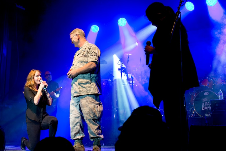 (Left) Vocalists, Julie Dutchak and Mari Anne Jayme, vie for the attention of U.S. Air Force Reserve Master Sgt. Jeff Walston, 913th Airlift Group, as they serenade him during a free concert by Gary Sinise and the Lt. Dan Band at Little Rock Air Force Base, Ark., April 29, 2016. The band, which is associated with the Sinise's charity foundation and the United Service Organizations, perform more than 40 concerts for military members and their families each year. (Courtesy photo by Eva Walston)