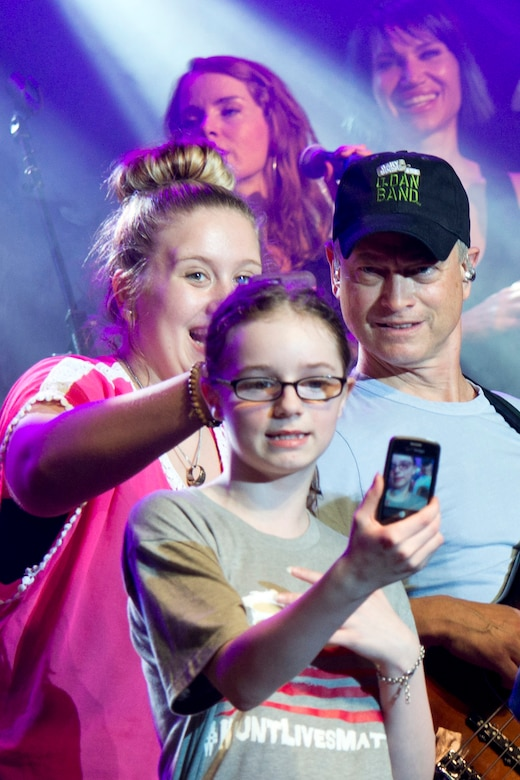 Actor and musician, Gary Sinise, engages with fans on stage as he performs with the Lt. Dan Band at Little Rock Air Force Base, Ark., April 29, 2016. The band, which is associated with the actor's charity foundation and the United Service Organizations, perform more than 40 concerts for military members and their families each year. (U.S. Air Force photo by Master Sgt. Jeff Walston)