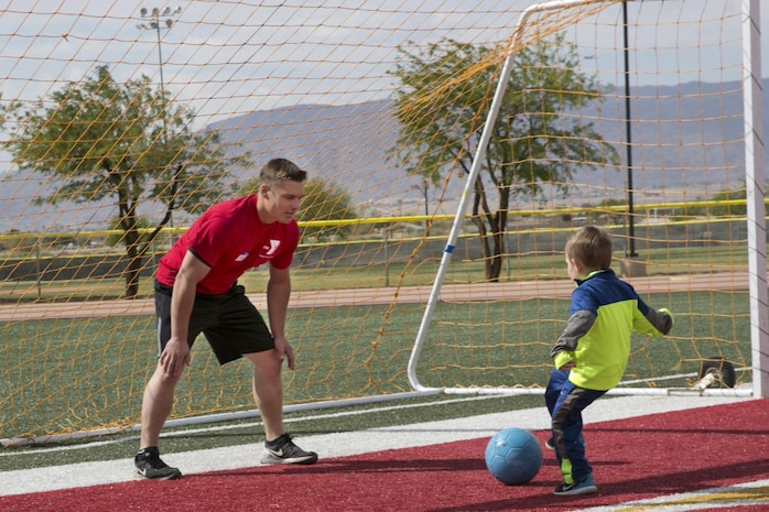 Lance Cpl. Kyle Cavatorta, tank crewman loader, 1st Tank Battalion, plays soccer with Noah Klich, 7, son of Staff Sgt. Mitchell A. Klich, technical control chief, Marine Corps Communication-Electronics School at the Healthy Kids Day hosted by Armed Services YMCA at Felix Field aboard the Combat Center April 30, 2016.  (Official Marine Corps photo by Lance Cpl. Dave Flores/Released)