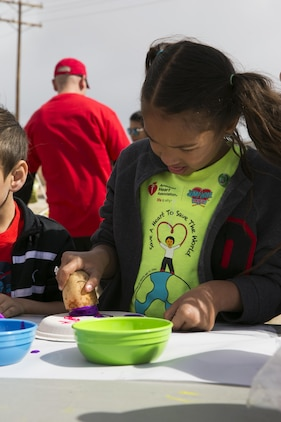 Gabriella Posey, 7, daughter of Rachael Posey, spouse, paints paper plates using stamps made from potatoes during the Healthy Kids Day hosted by the Armed Services YMCA at Felix Field aboard the Combat Center April 30, 2016. The children were able to express creativity as they learned about healthy foods.  (Official Marine Corps photo by Lance Cpl. Dave Flores/Released)