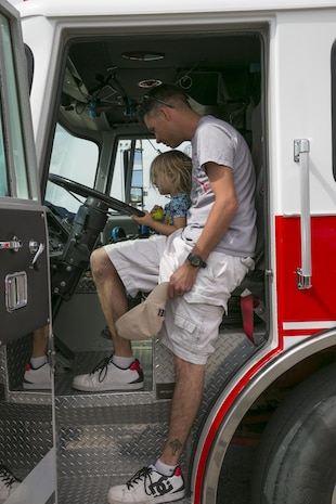 Sgt. Jeffery Walsh, roleplayer, Tactical Training Exercise Control Group, and his daughter Genevieve Walsh, 3, sit in the driver's seat of a Combat Center firetruck during the Healthy Kids Day hosted by the Armed Services YMCA at Felix Field aboard the Combat Center April 30, 2016. (Official Marine Corps photo by Lance Cpl. Dave Flores/Released)