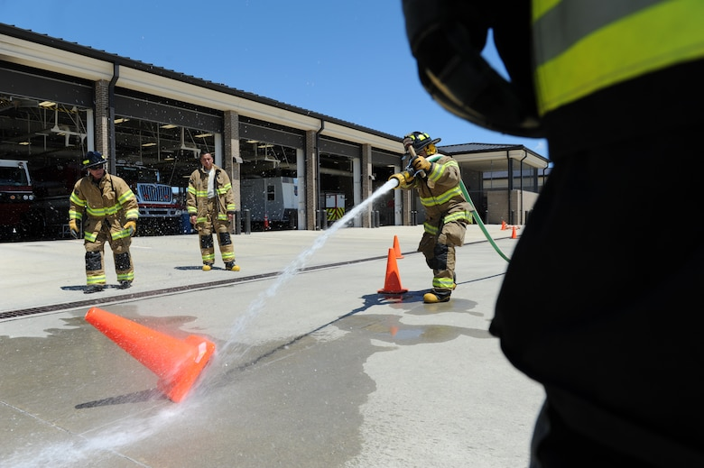Senior Airman Jonathan Martinez, 81st Infrastructure Division firefighter, knocks down a cone with a fire hose at the Keesler Fire Department as he trains for the 2016 Firefighter Combat Challenge Competition Wild Card Week, May 4, 2016, Keesler Air Force Base, Miss. Four members from the fire department competed in the qualifying round at Lake Charles, La., Apr. 30. (U.S. Air Force photo by Kemberly Groue)