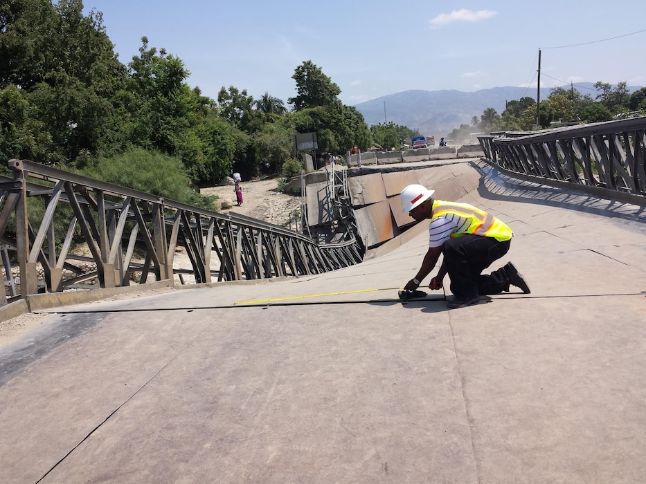 Project Manager Tim Brown measures and surveys portions of the collapsed Duviver Bridge during the Corps' visit to Haiti in April.