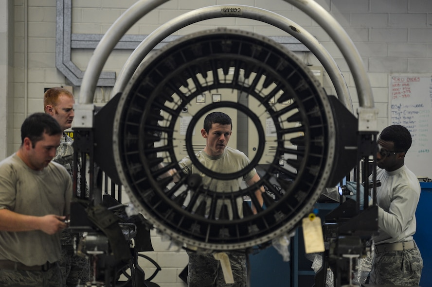 Airmen with the 52nd Aircraft Maintenance Squadron work on an engine at U.S. Air Forces in Europe's only F110 engine overhaul facility at Spangdahlem Air Base, Germany, April 19, 2016, during a weeklong civic leader trip to several bases in Europe. Air Force civic leaders are unpaid advisers, key communicators and advocates for the Air Force. (U.S. Air Force photo/Tech. Sgt. Joshua DeMotts)