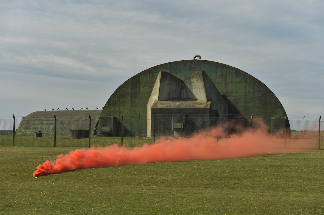 A smoke grenade marks the landing zone on the flightline of Royal Air Force Lakenheath, England, to start a combat search and rescue demonstration conducted for a group of Air Force civic leaders April 21, 2016. Air Force civic leaders are unpaid advisers, key communicators and advocates for the Air Force. (U.S. Air Force photo/Tech. Sgt. Joshua DeMotts)