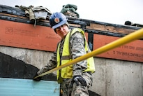 Air Force Staff Sgt. Casey Nowicki holds a tape measure to help calculate where to put molding tubes to pour concrete at Camp Hinds in Raymond, Maine, May 3, 2016. Nowicki is a structural craftsman assigned to the 110th Attack Wing Civil Engineering Squadron. The unit participated in Innovative Readiness Training, which helps airmen achieve wartime readiness while assisting the community. Air National Guard photo by Airman Tiffany Clark