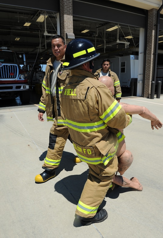 "Rusty Bell, 81st Infrastructure Division firefighter, completes a 100-foot ""dummy drag"" while receiving encouragement by Tech. Sgt. Jeremy Noah, 81st ID station chief, at the Keesler Fire Department as he trains for the 2016 Firefighter Combat Challenge Competition Wild Card Week, May 4, 2016, Keesler Air Force Base, Miss. Four members from the fire department competed in the qualifying round at Lake Charles, La., Apr. 30. (U.S. Air Force photo by Kemberly Groue)"