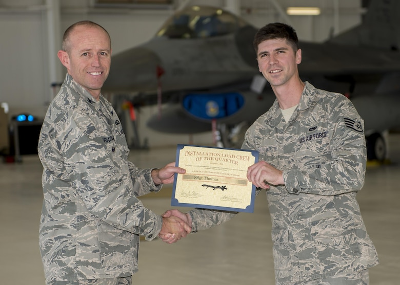 Col. Ryan Craycraft, the 49th Wing vice commander, presents an award to Staff Sgt. Thomas, a 49th Aircraft Maintenance Squadron load crew member from Holloman Air Force Base, N.M., after Thomas's team won the annual load completion here May 4. Teams from the 54th Fighter Group and the 49th Aircraft Maintenance Squadron here competed by testing their ability to quickly load training weapon systems onto their respective aircraft. (Last names are withheld due to operational requirements) (U.S. Air Force photo by Airman 1st Class Randahl J. Jenson)