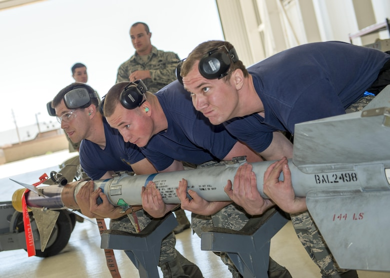 From left to right: Senior Airman Caleb, Staff Sgt. Josh and Senior Airman Matthew, 54th Fighter Group weapons load crew members from Holloman Air Force Base, N.M., lift a training missile during the annual load competition here May 4. Teams from the 54th Fighter Group and the 49th Aircraft Maintenance Squadron here competed by testing their ability to quickly load training weapon systems onto their respective aircraft. (Last names are withheld due to operational requirements) (U.S. Air Force photo by Airman 1st Class Randahl J. Jenson)