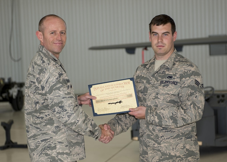 Col. Ryan Craycraft, the 49th Wing vice commander, presents an award to Senior Airman Christopher, a 49th Aircraft Maintenance Squadron load crew member from Holloman Air Force Base, N.M., after Christopher's team won the annual load completion here May 4. Teams from the 54th Fighter Group and the 49th Aircraft Maintenance Squadron here competed by testing their ability to quickly load training weapon systems onto their respective aircraft. (Last names are withheld due to operational requirements) (U.S. Air Force photo by Airman 1st Class Randahl J. Jenson)