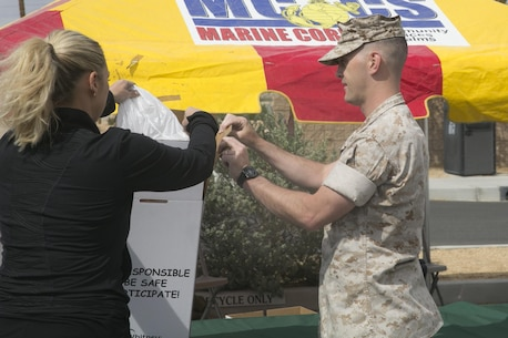 Staff Sgt. Joshua Gerland, physical security chief, Provost Marshal's Office, helps a Combat Center patron dispose of their prescription medications during the PMO Prescription Drug Take Back held at the base exchange parking lot April 30, 2016. (Official Marine Corps photo by Cpl. Thomas Mudd/Released)