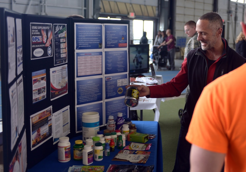 Cliff McArthur, 28th Medical Group dietitian, discusses supplements with families at the Pride Hangar during the Discover the Hills portion of Wingman and Spouse Appreciation Day at Ellsworth Air Force Base, S.D., April 29, 2016. McArthur is promoting the Health and Wellness Center with his booth, providing information about supplements and supplement safety. (U.S. Air Force photo by Airman Donald Knechtel/Released)