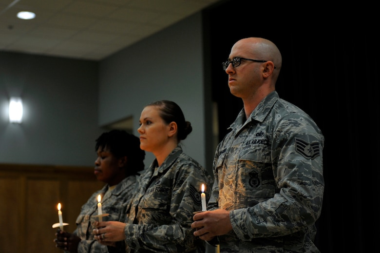 U.S. Air Force Airmen participate in the candle lighting portion of the Holocaust Remembrance Ceremony May 5, 2016, at Little Rock Air Force Base.  Lighting a candle signifies passing the light of memory and hope from one person to another. (U.S. Air Force photo by Kevin E. Sommer Giron)