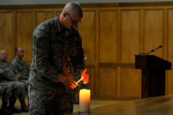 U.S. Air Force Staff Sgt. Austin Babcock-Kochera, 19th Security Forces, lights a candle during the Holocaust Memorial Ceremony May 5, 2016, at Little Rock Air Force Base. The candle lighting portion of the ceremony was in remembrance of the 6 million Jews who were killed during the Holocaust.  (U.S. Air Force photo by Kevin E. Sommer Giron)