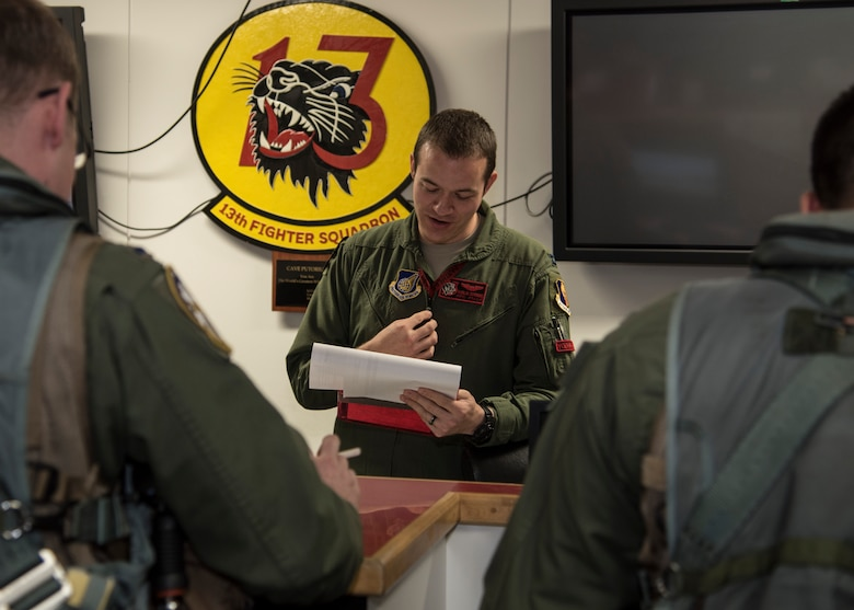 U.S. Air Force Capt. Philip Downing, an F-16 Fighting Falcon pilot with the 13th Fighter Squadron, briefs pilots on the status of F-16s at Misawa Air Base, Japan, May 4, 2016. Downing acts as a conduit between pilots and maintainers so all information regarding the safety and condition of the aircraft is accurately relayed. (U.S. Air Force photo by Airman 1st Class Jordyn Fetter)